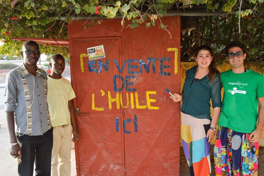Two volunteers on a Micro-finance volunteer opportunity abroad with the stall that they helped a beneficiary open in Senegal.